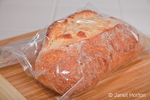 Loaf of three cheese bread stored in zipped plastic bag, resting on a bread board on a tile counter