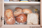 Variety of breads stored in plastic bags in cupboard in kitchen