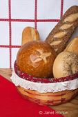 Variety of home made breads in a cloth-lined wicker basket, including sourdough bread bowl, french baguette, three seed loaf and an everything bagel