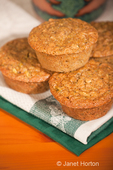 Zucchini muffins stacked on tea towels on a wood table, with a coffee mug in the background
