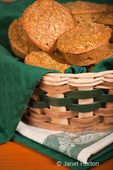 Zucchini muffins stacked in a cloth-lined wicker basket, resting on tea towels on a wood table