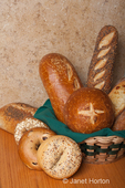 Variety of home made breads, with some in a wicker basket with a cloth napkin, including sourdough bread bowl, sourdough loaf, three seed loaf, three cheese loaf, stone milled rye loaf, everything bagel, cinnamon swirl and raisen bagel and whole grain bagel