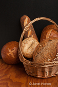 Variety of home made breads, with some in a wicker basket, including sourdough bread bowl, sourdough loaf, three seed loaf, stone milled rye loaf, whole grain loaf and everything bagel