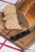 Loaf of stone milled rye bread with slices, on a wood cutting board on a tea towel, with a bread knife
