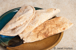 Pita loaves folded in half, resting on a pottery plate