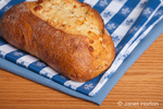 Loaf of three cheese bread, resting on cloth napkins