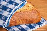 Loaf of three cheese bread, partially wrapped by a blue checkered cloth napkin