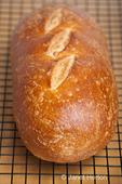 Loaf of sourdough bread on a cooling rack