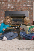Boy and girl reading in front of a gas fireplace in a family room