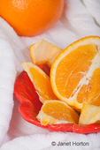 Whole orange, half an orange, orange slices and peel in a bowl in a spa setting for aromatherapy purposes