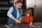 Grandmother, Sue, mixing cookie dough with four year old grandaughter, Islay, looking on