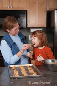 Grandmother, Sue, holding spoon for four year old granddaughter, Islay, to lick, while making cookies