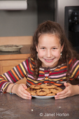 Eleven year old girl, Matisse, with plate of freshly made cookies that she made