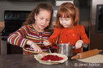 Two sisters, 11 and 4 years old, adding cherry pie filling to pie crust, with the older one teaching the younger what to do