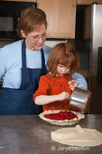 Four year old girl, Islay, adding cherry pie filling into pie shell with grandmother, Sue, assisting