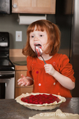 Four year old girl, Islay, licking spoon from filling a cherry pie