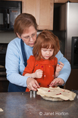 Grandmother, Sue, and four year old granddaughter, Islay, adding pie dough topping with shapes cut out, to cherry pie
