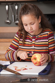 Eleven year old girl, Matisse, using apple peeler to peel apple