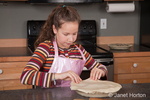 Eleven year old girl, Matisse, placing pie dough on top of pie