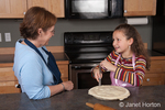 Eleven year old girl, Matisse, trimming excess pie crust from edge of pie