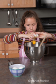Eleven year old girl, Matisse, breaking an egg and putting it in a bowl to make brownies