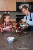 Eleven year old girl, Matisse, pouring bowl of brownie mix into pan they will be baked in