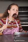 Eleven year old girl, Matisse, licking brownie mix off of spoon