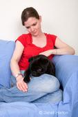 Woman, Thea, cuddling her black Pug, Bean
