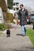 Woman walking her black Pug in an urban area