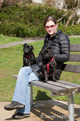 Woman sitting on a park bench with her two black Pugs, Bean and Frank