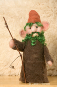 Gnome made of dry felted (needle felted) colored sheep's wool with mohair locks for hair and beard, holding a stick for a walking staff.