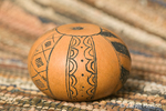 The design was scratched into a dry gourd with a sharpened nail and then black ash was rubbed into the scratched areas.