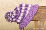 Hand-knitted purple and white hat, resting on the back of a wood chair