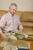 Man, Robert, doing card weaving, making a belt in his home