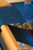 Close-up of a textile that is a double-layer double weave, blue and black layers being woven