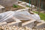 Freshly planted terraced kitchen garden covered with plastic over hoops