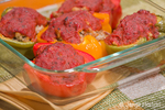 Baking dish of sausage stuffed bell peppers, covered with tomato sauce