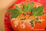 Broiled cheese-covered tomato in a decorative red bowl