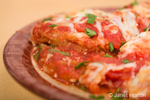 Plate of eggplant parmesan with fresh parsley sprinkled on top, on a plate