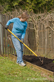Woman, Kath, using a rake to spread compost in her small kitchen garden