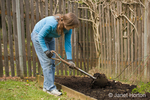 Woman, Kath, using shovel to mix compost into the soil of a small kitchen garden
