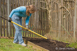 Woman, Kath, using rake to spread and level the compost in a small kitchen garden