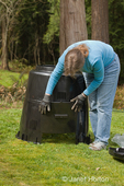 Woman, Kath, assembling the pieces of a compost bin in her wooded backyard