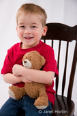 Three year old boy, Joshua, hugging teddy bear while sitting in rocking chair