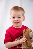 Three year old boy, Joshua, hugging teddy bear