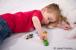 Three year old boy playing with toy cars