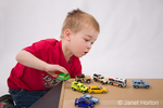 Three year old boy, Joshua, playing with toy cars