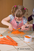 Five year old girl grating carrots, assisted by her mother, for a carrot cake