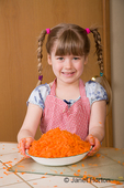 Five year old girl proudly holding a bowl of grated carrots that she helped her mother grate