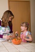 Mother and daughter laughing while pouring brown sugar into mixing bowl, while making carrot cake